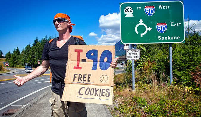 Matthew Karsten hitchhiking in the USA holding a sign offering free cookies