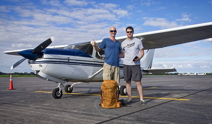 Two guys posing in front of an airplane with a backpack and a thumbs up