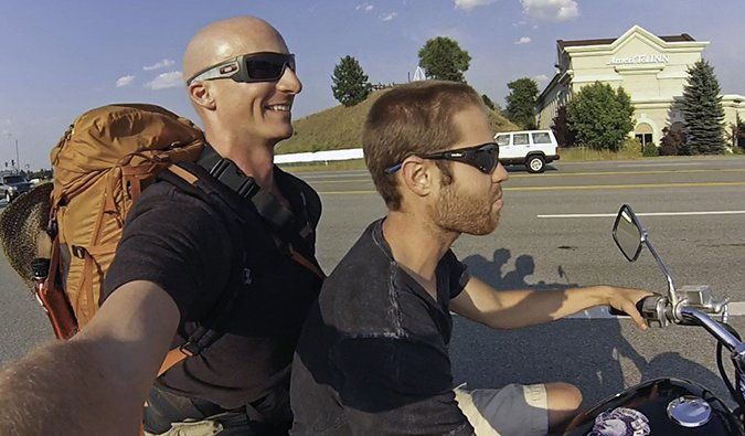 Two guys on a motorcycle, on a motorcycle owner, the other is a hitchhiker in America