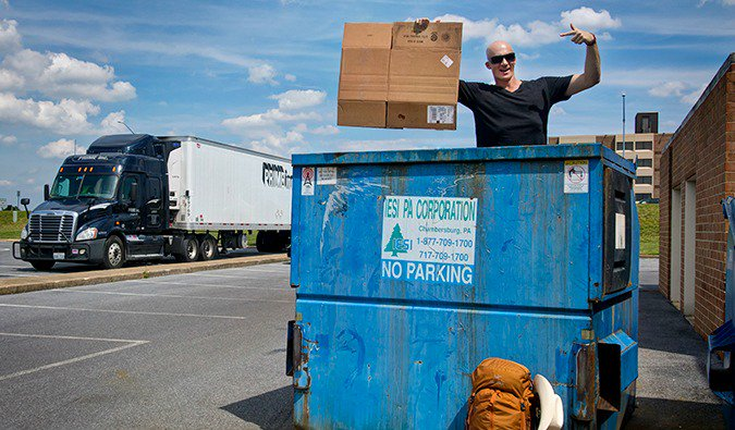 Guy in a dumpster holding up a piece of cardboard for his hitchhiking sign with a truck passing