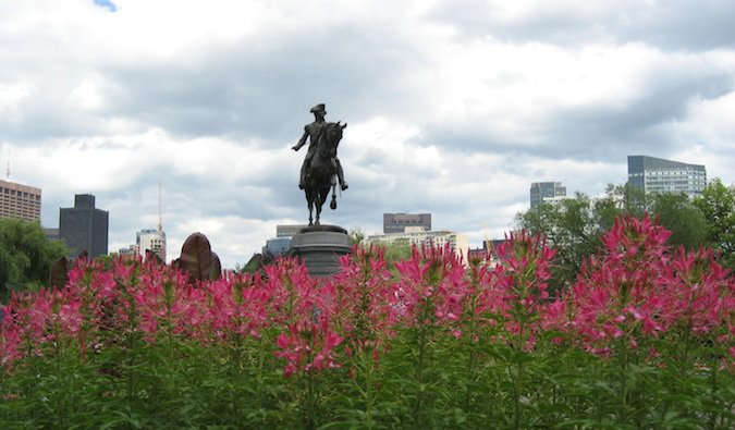 a historic statue surrounded by flowers in boston