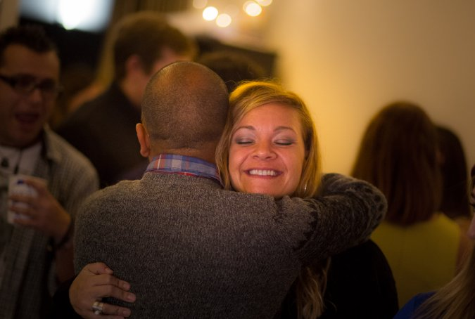 Candid travel picture of two people hugging at a party