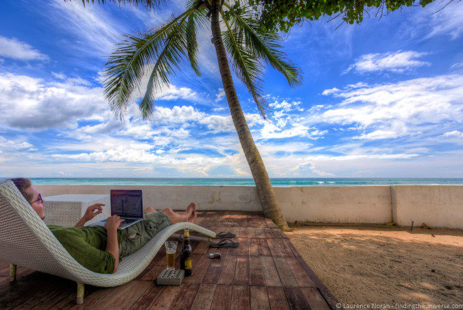 Remote worker working on a laptop traveling to a beach location