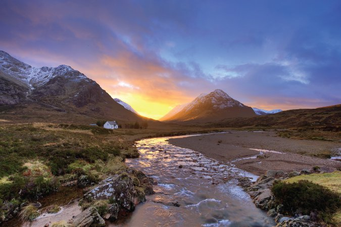 Photo of the sunsetting behind mountains in Glencoe, Scotland with a house in the midground