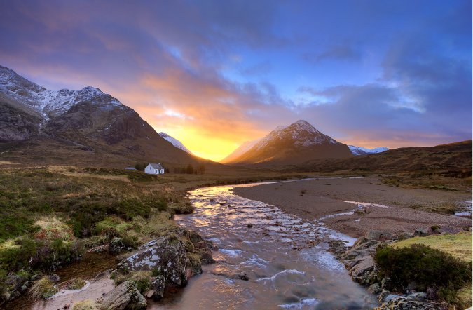 Photograph of a river and mountain and a colorful sunset