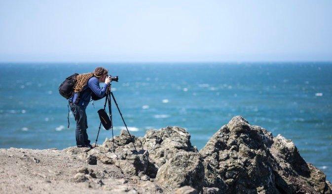 Photographer and gear set up near the ocean