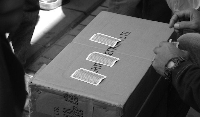 A black and white photo of the 3 card monte scam travel