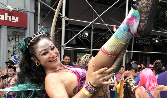 a woman with a hula hoop and dressed in glitter during gay pride parade