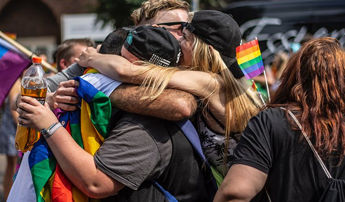women hugging in the middle of a pride parade