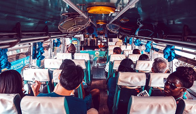 people aboard a crowded bus in Thailand with fans attached to the ceiling