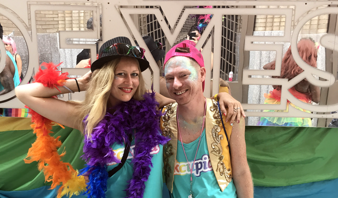 Dani and Adam pose in front of a gay pride parade float in New York City