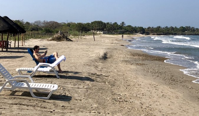 A sandy beach with a couple of tourists relaxing on a sunny day in Cartagena