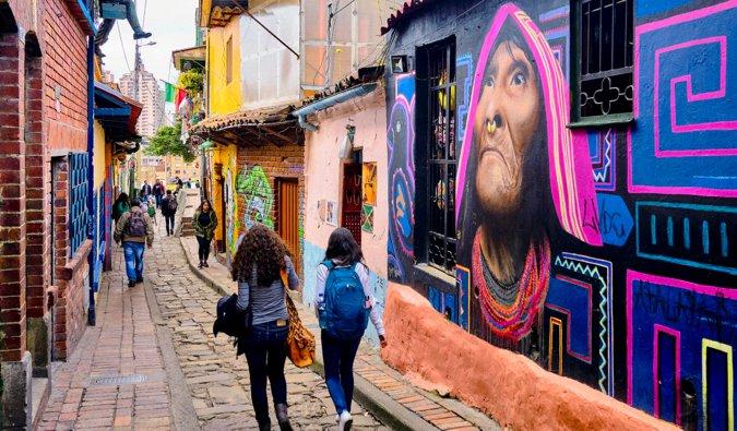 two women walking through streets of graffiti in Bogota