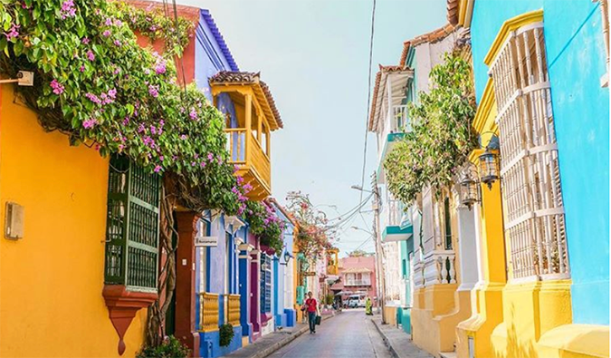 Brightly painted houses with hanging flower gardens lining a narrow street in Cartagena, Colombia