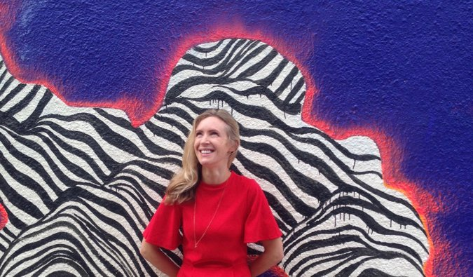 Best selling author Helen Russell posing in front of a colorful mural