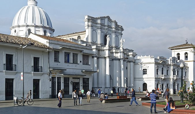 white buildings in Popayán with people walking around the main town plaza
