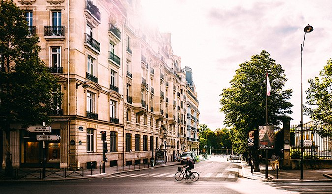 a man cycling across an intersection in the streets of Paris