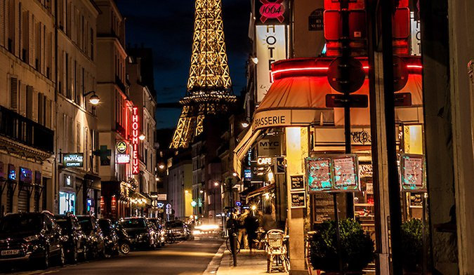 people walking in front of the Eiffel Tower at night