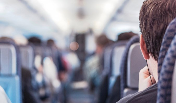 A man sitting alone on a busy airplane mid flight