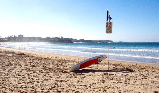 A lone surfboard resting in the sand on the stunning Manly Beach