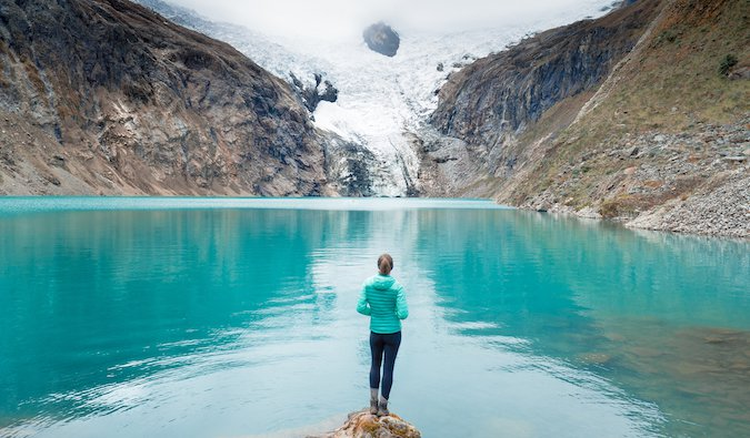 Kristin Addis posing in front of a bright blue lake in the mountains