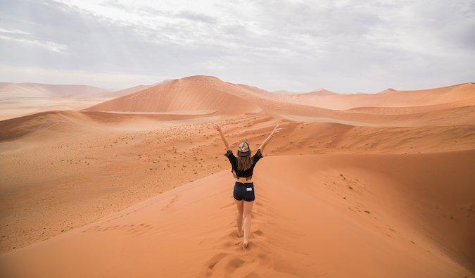 Kristin Addis walking across sand dunes in the desert