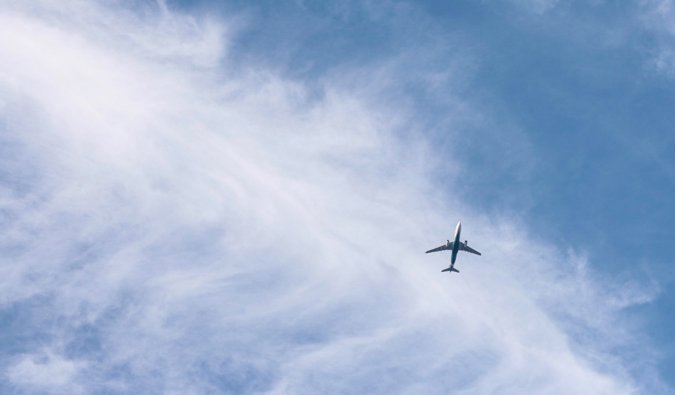 A commercial jet flying high in the bright blue sky