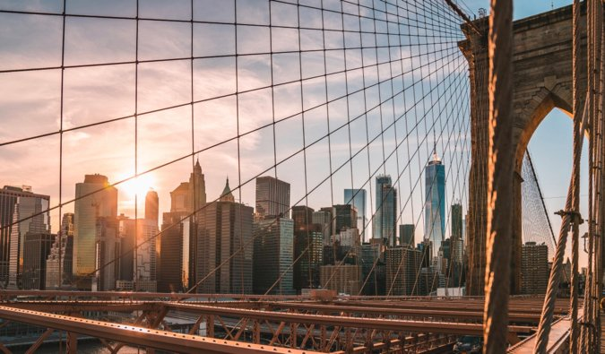 A shot of Manhattan from the Brooklyn Bridge during sunset in the summer