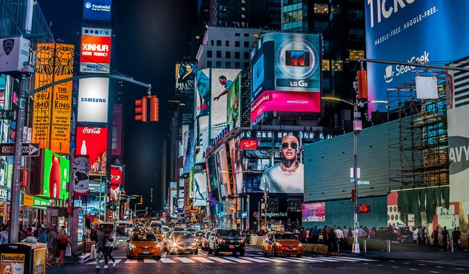 Times Square in NYC lit up at night and bustling with people