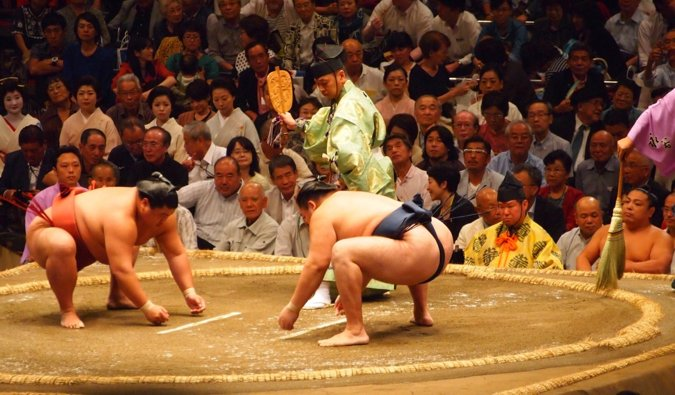 Two sumo wrestlers about to fight in a massive arena as the crowd watches in Japan