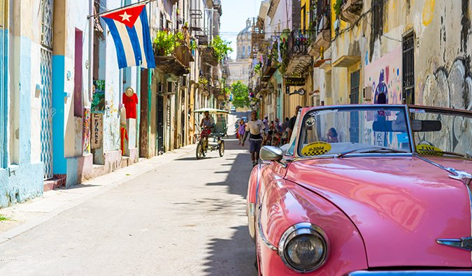 a classic pink car in Cuba on a busy street