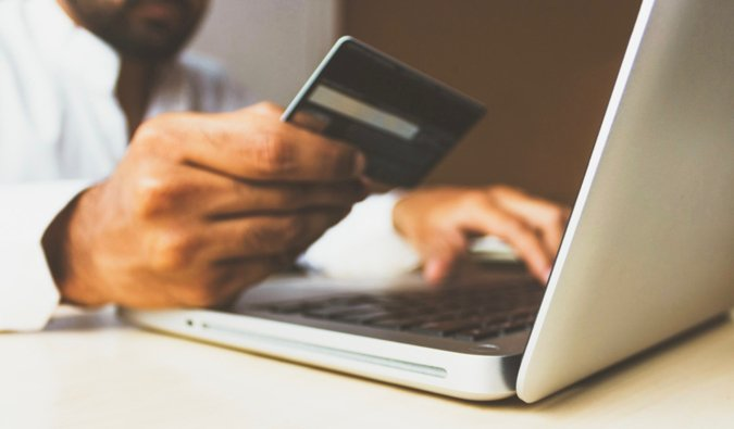 a man holding a credit card making an online purchase