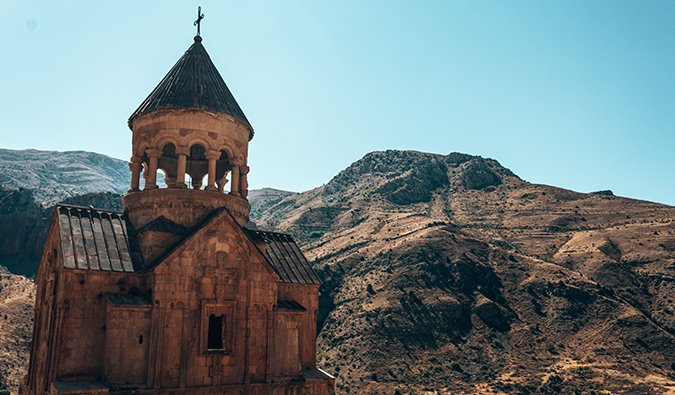 a church with a mountain backdrop in Armenia