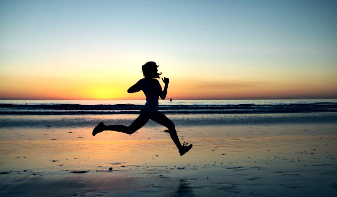 A lone runner sprinting on a beach at sunset