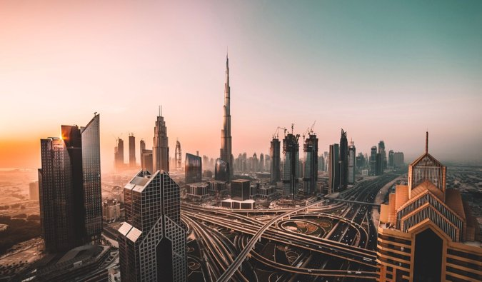 The massive Burj Khalifa and surrounding skyscrapers and roads in Dubai at sunrise