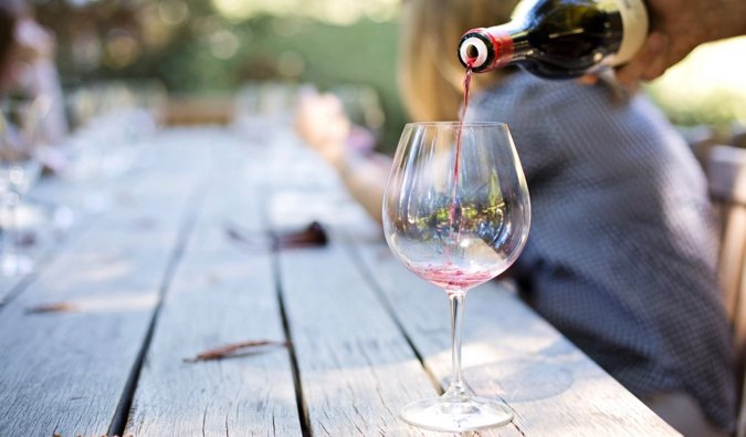 A glass of wine being poured on a table outside in Napa Valley, USA