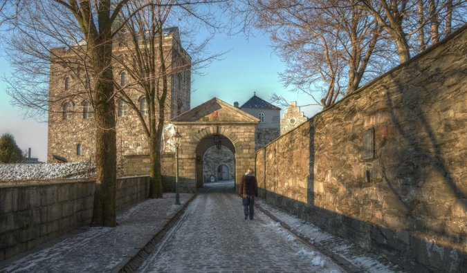 A traveler explores the historic Bergenhus Fortress in Bergen, Norway