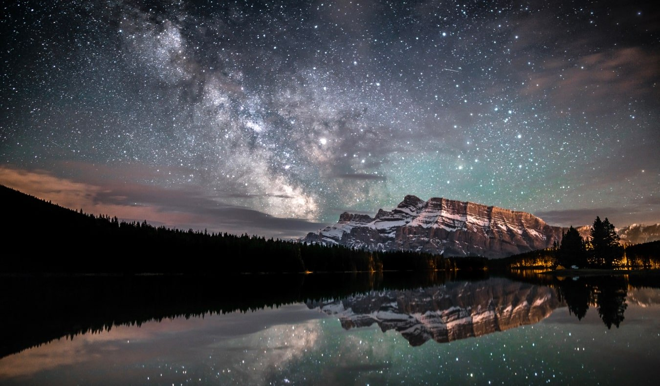 Lake Louise and Banff at night under a starry sky