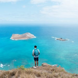 A man with a backpack on a cliff staring at two small islands in the ocean