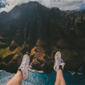 two legs with sneakers hanging off a clilff over looking a lush Hawaiian mountain