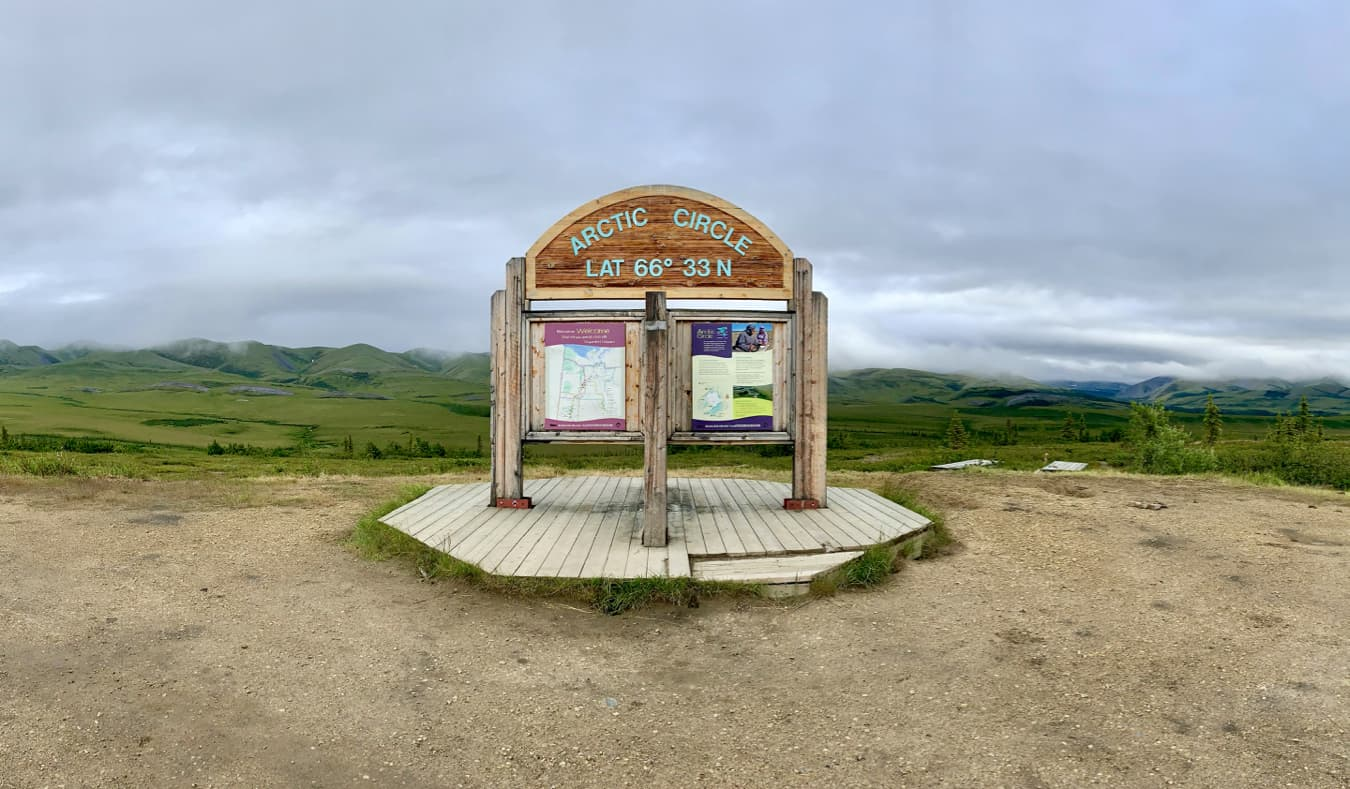 A wooden sign declaring the Arctic Circle in Yukon, Canada
